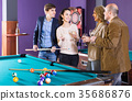 Mature and young couples hanging out in billiard club together 35686876