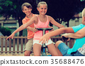 Children are teetering on the swing 35688476