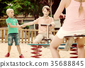 children are teetering on the swing in the playground. 35688845