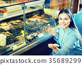 brunette girl buying dark and white chocolate with fillings 35689299