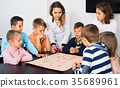 Boys and little girls playing at board game 35689961