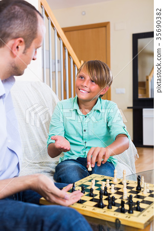 Man and teenager son playing chess. 35690382
