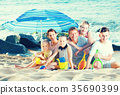 Large family together on beach sitting under umbrella 35690399