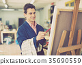 Man near easel painting on canvas 35690559