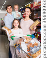 parents with kids choosing biscuits 35690933