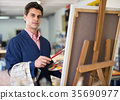 Man near easel painting on canvas 35690977