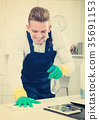 Handsome guy in uniform cleaning in office 35691153