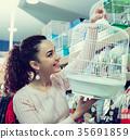 Portrait of happy girl choosing bird cage 35691859