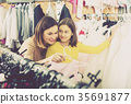 Woman 25-29 years old with girl 10-15 years old are choosing comfortable dress 35691877