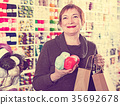 Woman holding shopping bags and accessories for knitting and embroidery 35692678