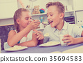 Sister with brother are playing with food 35694583