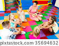 Kids sitting around teacher with small guitar 35694632