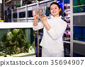 Girl keeps big tropical fish in plastic container 35694907
