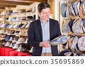 portrait of positive male try on flat hat at the shopping mall 35695869