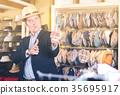 portret of smiling young guy try on panama at headwear store 35695917
