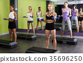 Females performing aerobics with dumbbells at fitness center 35696250