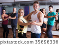 Dancing couples learning salsa 35696336
