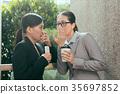 Asian women talking about office gossip 35697852