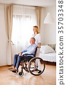 Nurse and senior man in wheelchair during home 35703348