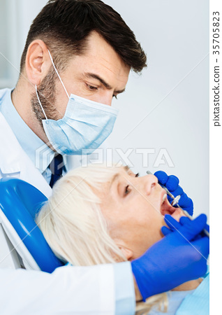 Concentrated dentist in the process of teeth 35705823