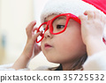 Little girl dressed in a santa claus hat and 35725532