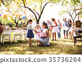 Family celebration or a garden party outside in 35736264