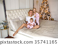mother with two daughters in their pajamas sitting 35741165