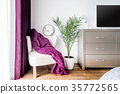 Armchair, purple blanket and a wall clock as decor 35772565