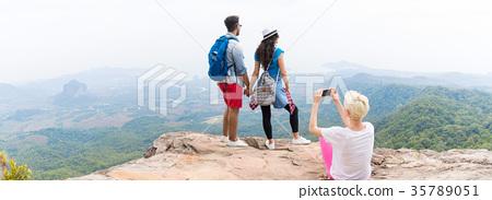 Girl Taking Photo Of Couple With Backpacks Posing 35789051