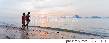 Couple Holding Hands Walking On Beach At Sunset 35789151