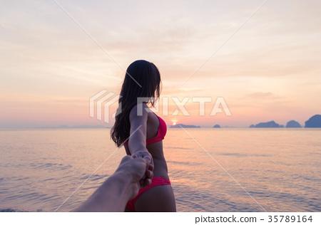Woman Hold Man Hand Walking On Beach At Sunset 35789164