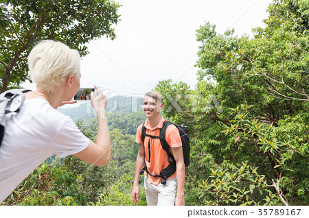 Girl Taking Photo Of Guy With Backpack Posing Over 35789167