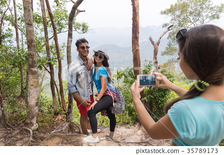 Girl Taking Photo Of Couple With Backpacks Posing 35789173