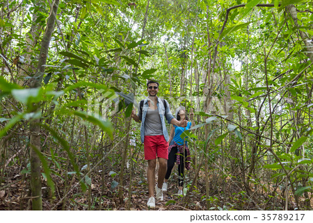 Couple With Backpacks Trekking On Forest Path 35789217