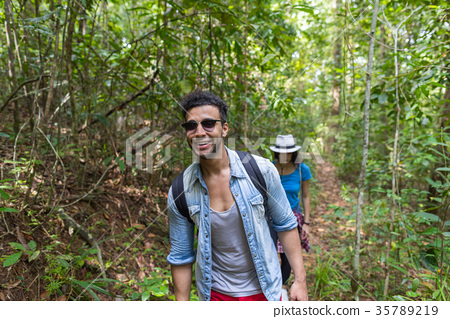 Couple With Backpacks Trekking On Forest Path 35789219