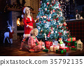 Child at Christmas tree. Kids at fireplace on Xmas 35792135