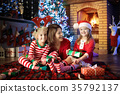 Family with kids at Christmas tree and fireplace. 35792137