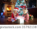 Child at Christmas tree. Kids at fireplace on Xmas 35792138