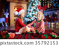 Child at Christmas tree. Kids at fireplace on Xmas 35792153