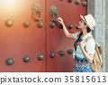 woman play knock wooden red door 35815613