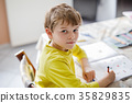 Happy school kid boy at home making homework 35829835