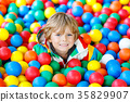 Little kid boy playing at colorful plastic balls 35829907