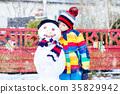 Funny kid boy making a snowman in winter 35829942