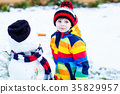 Funny kid boy in colorful clothes making a snowman 35829957