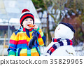 Funny kid boy in colorful clothes making a snowman 35829965