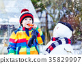Funny kid boy in colorful clothes making a snowman 35829997