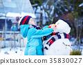 Funny kid boy making a snowman in winter 35830027