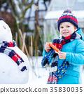 Little kid boy making a snowman in winter 35830035