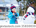 Funny kid boy making a snowman in winter outdoors 35830039