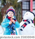Funny kid boy making a snowman in winter outdoors 35830046
